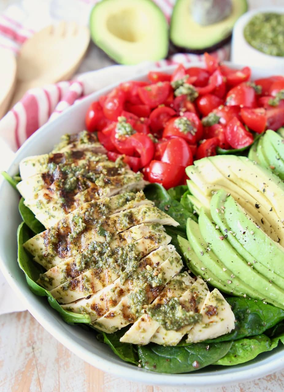 Sliced pesto chicken, avocado and tomatoes on top of a spinach salad in a bowl