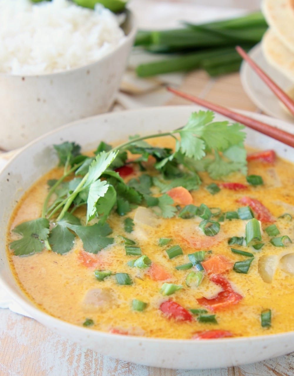 Yellow curry in bowl, topped with fresh cilantro sprigs, with bowl of rice on the side