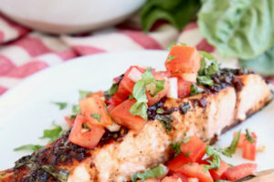 Bruschetta topped baked salmon fillet on white plate with copper fork