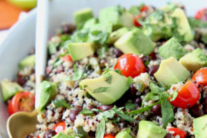 Quinoa salad in bowl with white and gold spoon