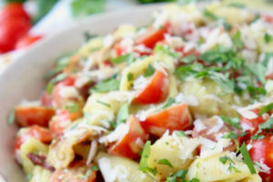 Shell pasta salad with cherry tomatoes in bowl topped with fresh chopped basil