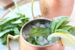 Moscow mules in copper mugs with lemon wedges and basil leaves