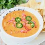 Queso dip in white bowl with tortilla chips on the side