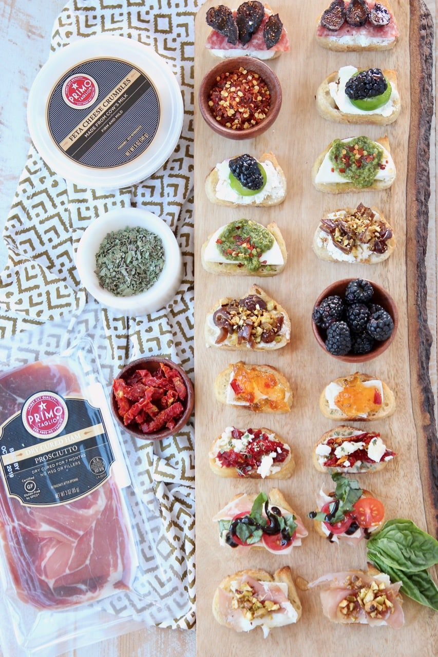 Overhead shot of crostini with different toppings on wood cutting board