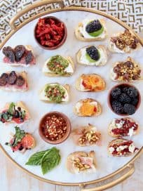 Crostini with various toppings on marble and gold cutting board