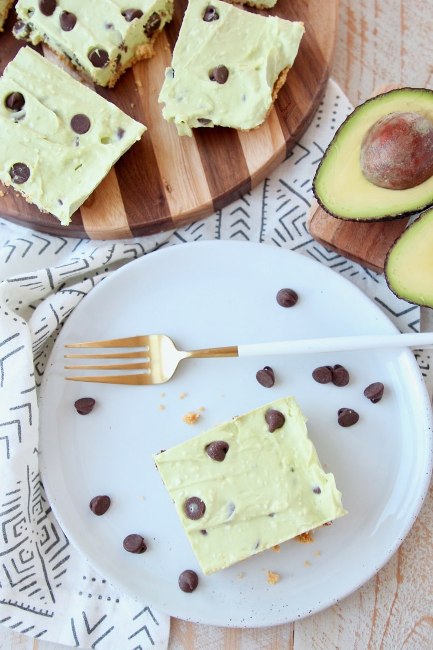 Overhead shot of avocado cheesecake bars on plate and cutting board with chocolate chips and halved avocado
