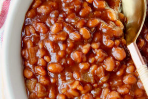 BBQ baked beans in bowl with serving spoon in the beans