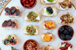 Crostini with various toppings on marble serving tray