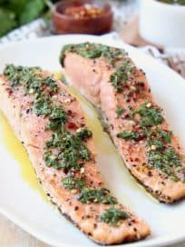 Two pieces of salmon on plate topped with chimichurri sauce