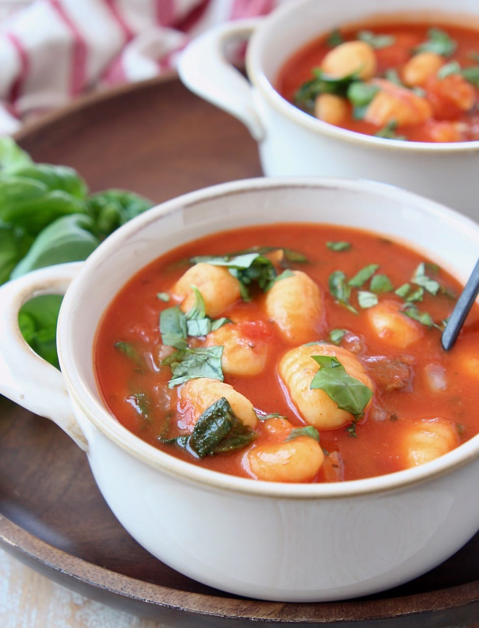Tomato basil gnocchi soup in white bowls with spoons