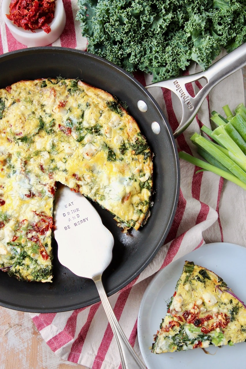 Frittata in skillet, with slice cup out on plate to the side