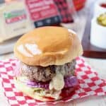 Juicy lucy burger on bun with onion and lettuce