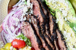 Grilled steak salad in bowl with avocado slices and sliced onions