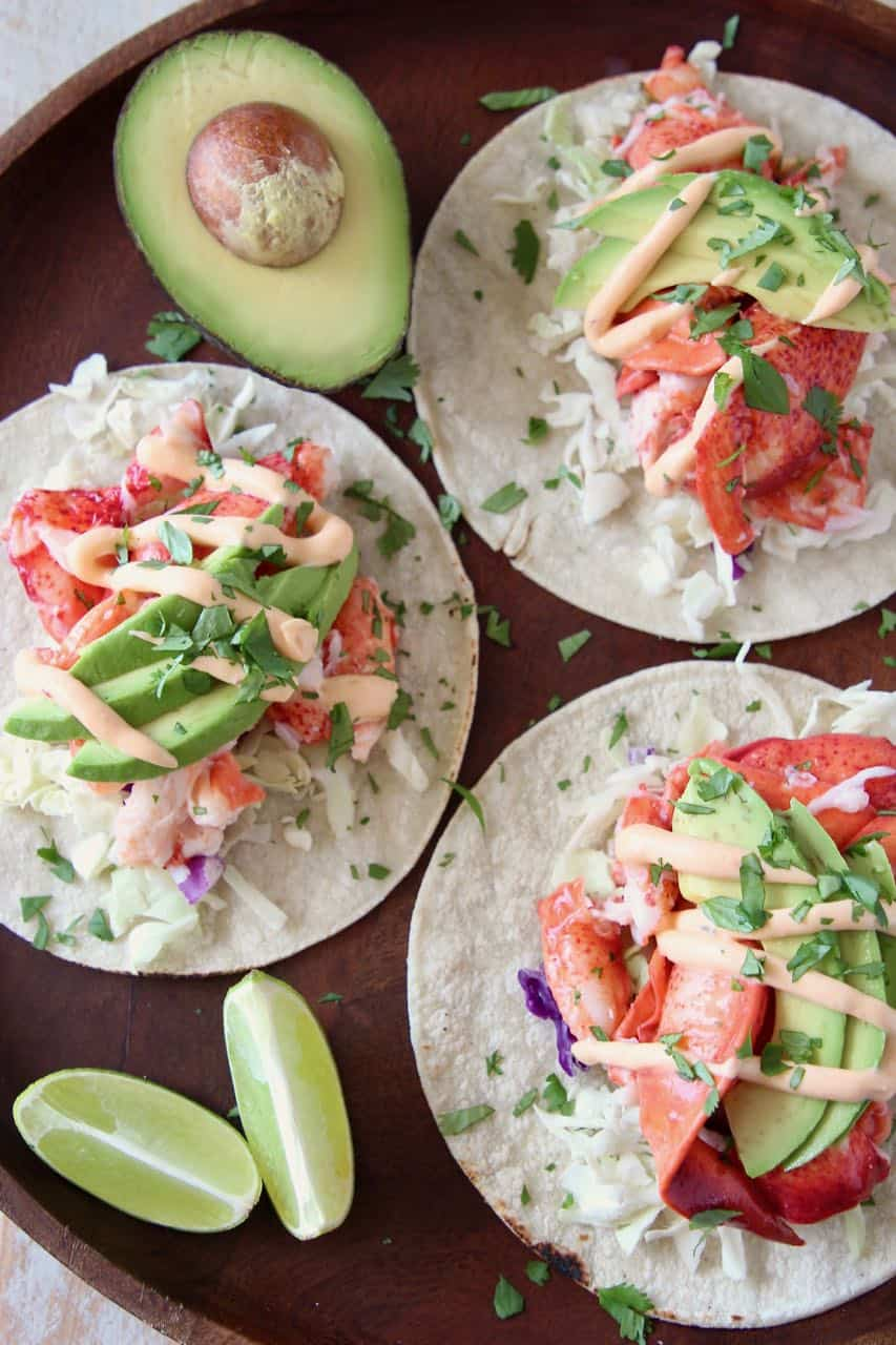 Overhead image of lobster tacos on wood tray with lime wedges and half an avocado