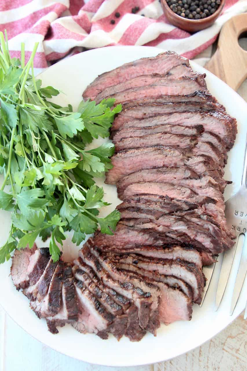 Sliced tri tip steak on white plate with fresh parsley