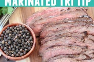 Thinly sliced tri tip on wood cutting board with black peppercorns