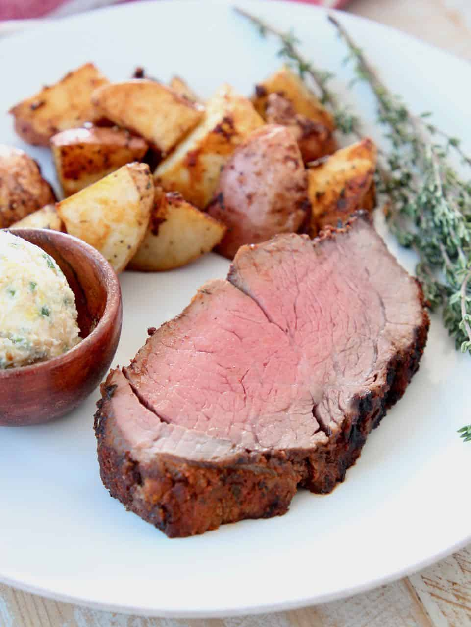 Thick sliced beef tenderloin on plate with herbs, potatoes and butter