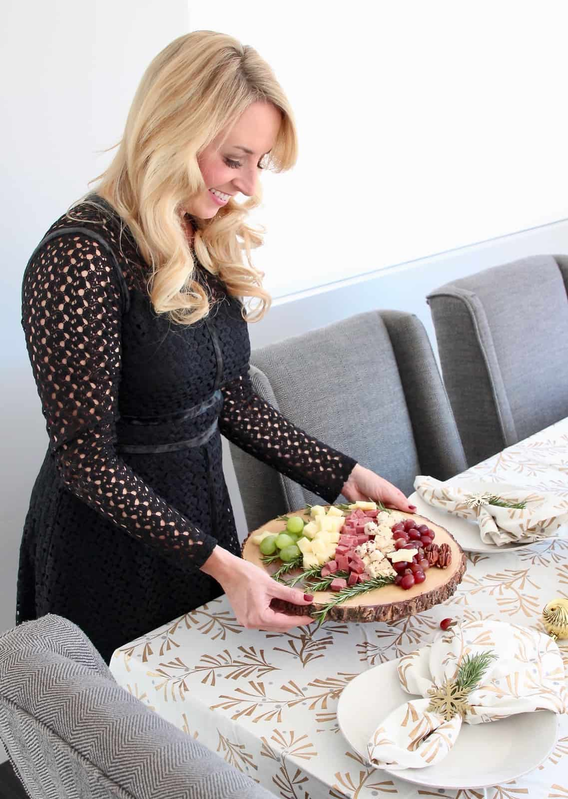 Woman serving holiday cheese board on dining room table