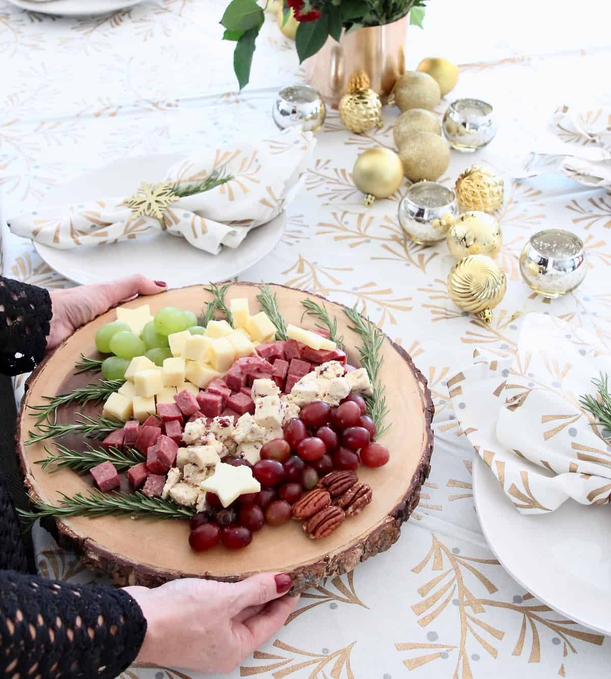 Hands holding Christmas tree holiday cheese board