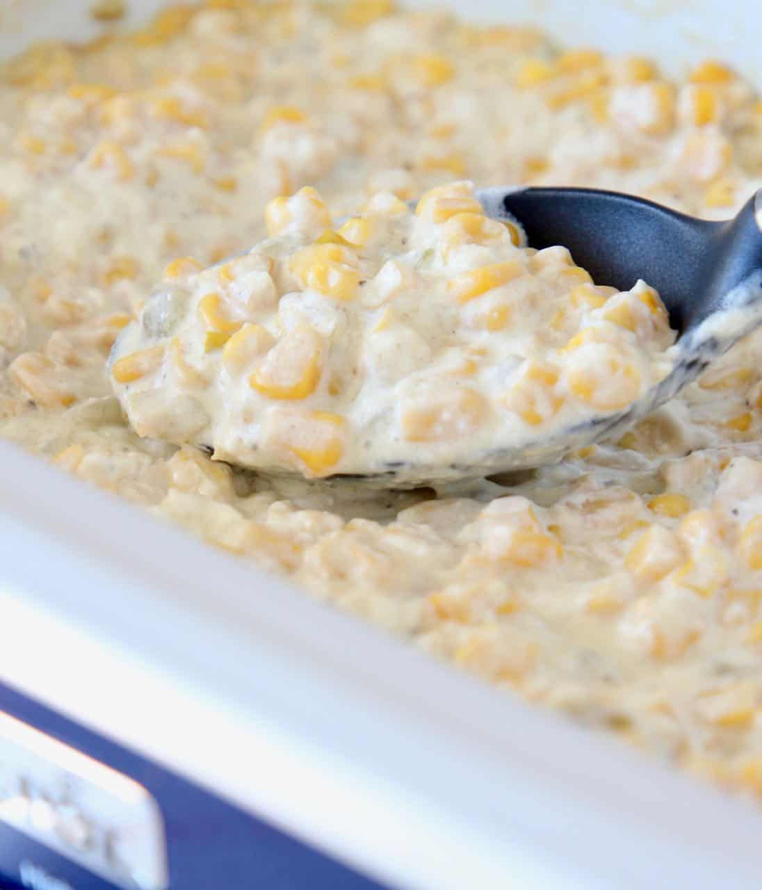 Creamed corn in crock pot with serving spoon