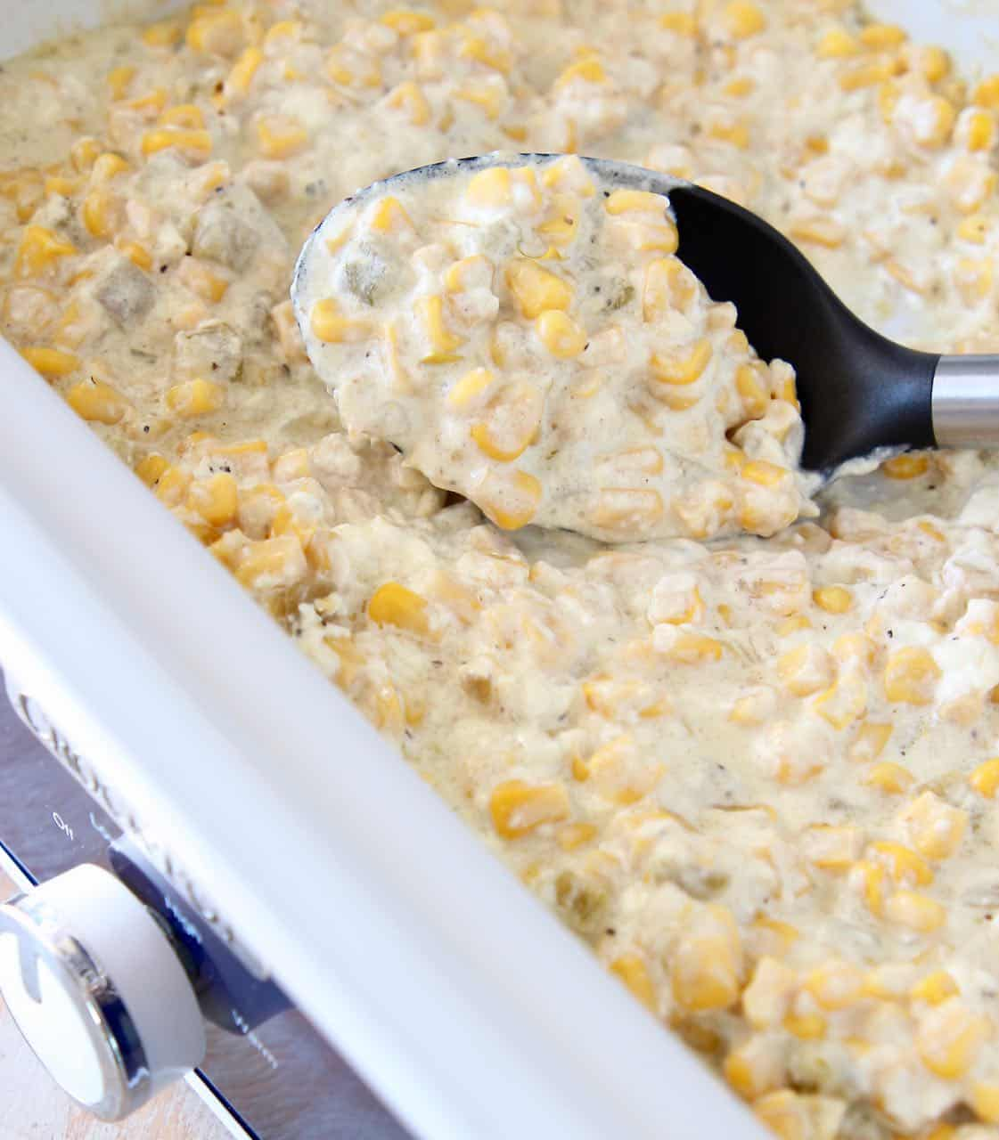 Creamed corn in slow cooker with serving spoon