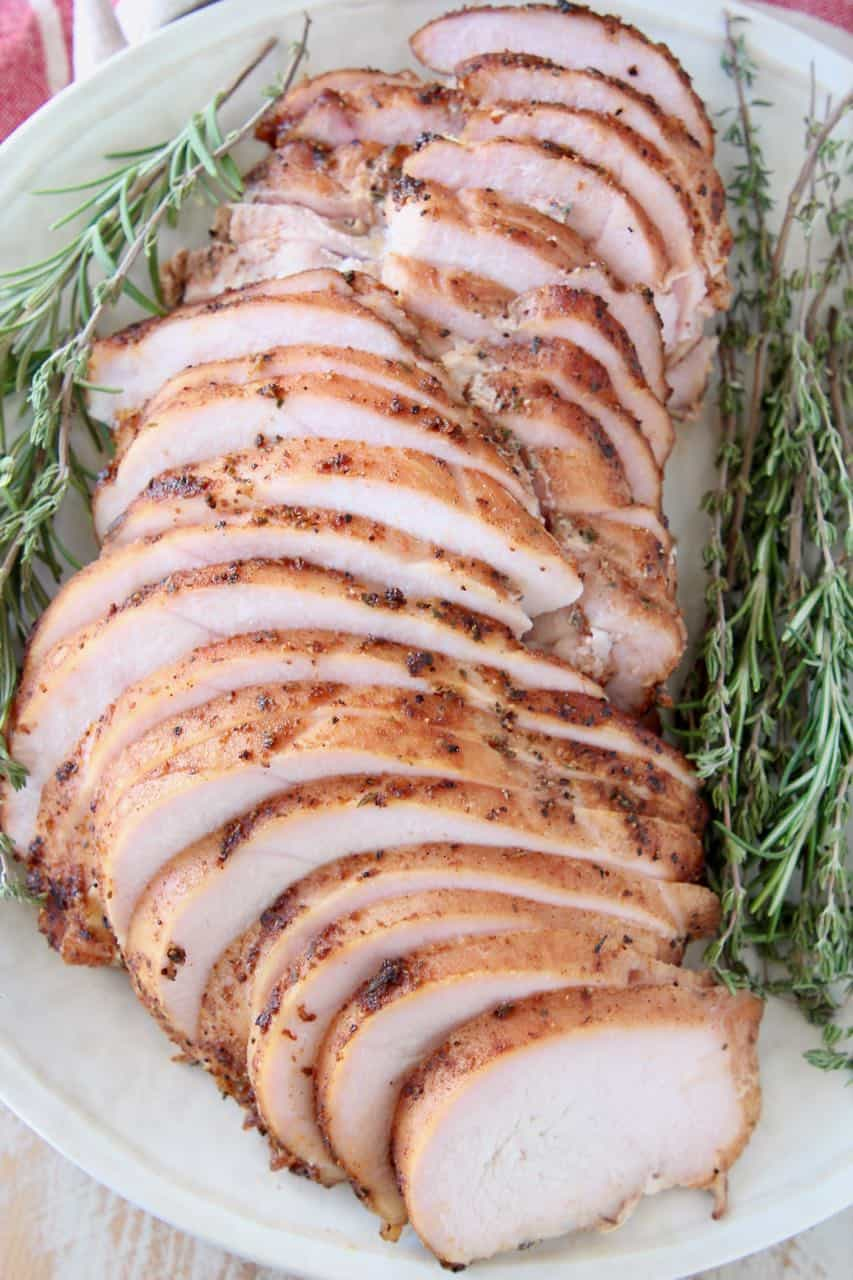 Sliced smoked turkey breast on plate with fresh herbs