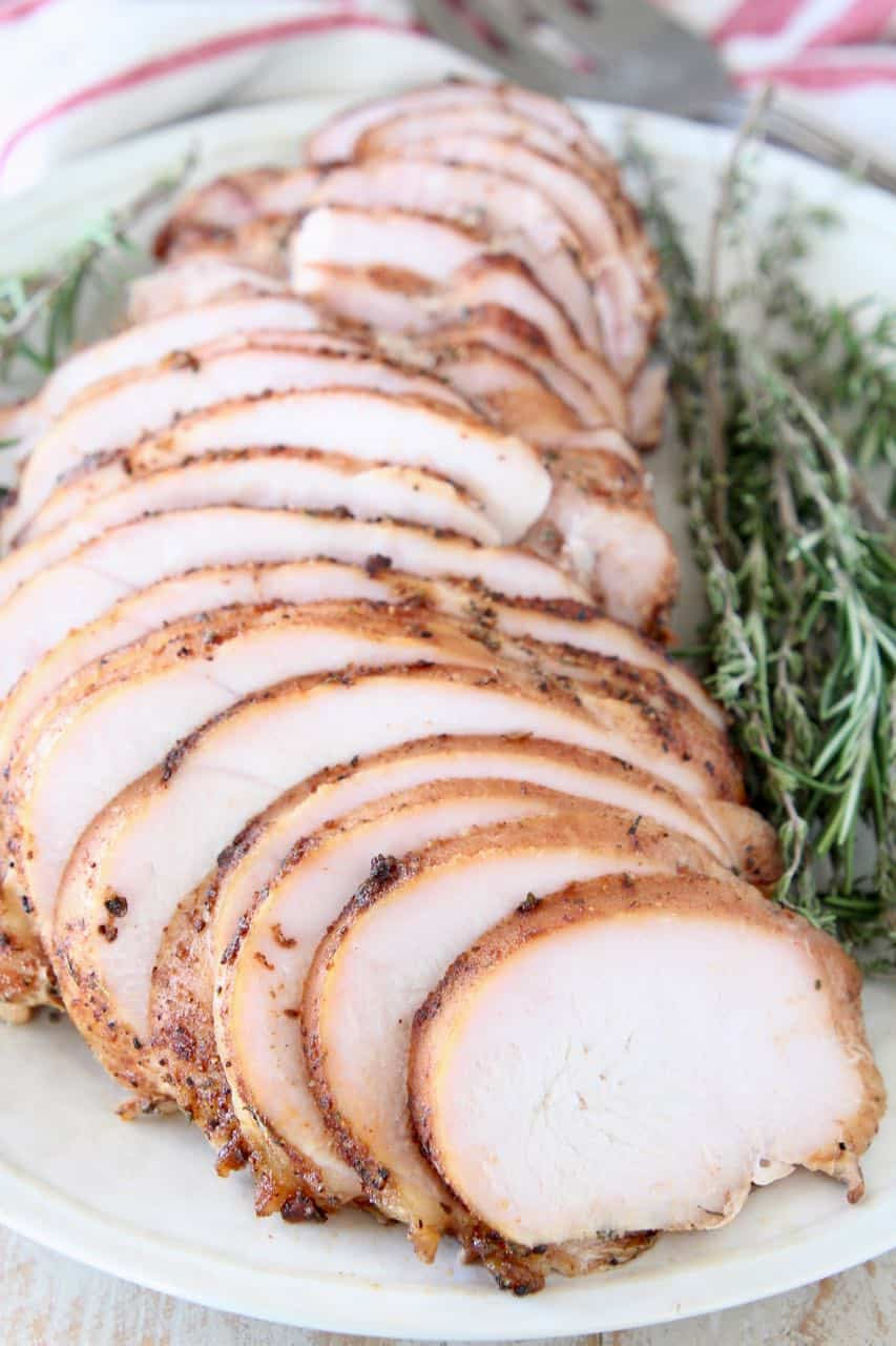 Sliced turkey breast on plate with fresh rosemary and thyme sprigs