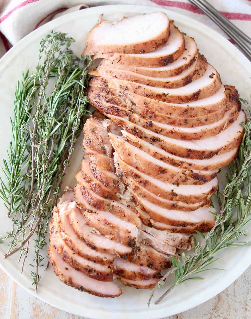 Slices of smoked turkey breast meat on plate with fresh herbs