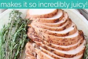 Sliced turkey breast meat on plate with fresh herbs