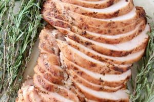 Sliced smoked turkey breast on plate with fresh rosemary and thyme sprigs