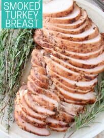 Sliced turkey breast on plate with fresh herbs