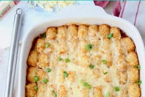 Tater tot casserole in baking dish with spatula