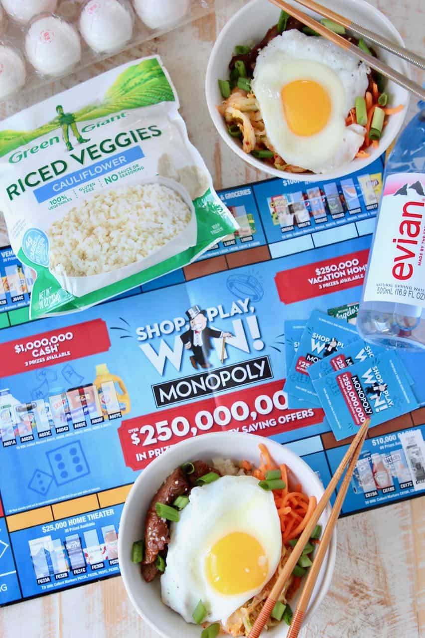 Korean BBQ rice bowls topped with fried egg, sitting on Albertsons monopoly board