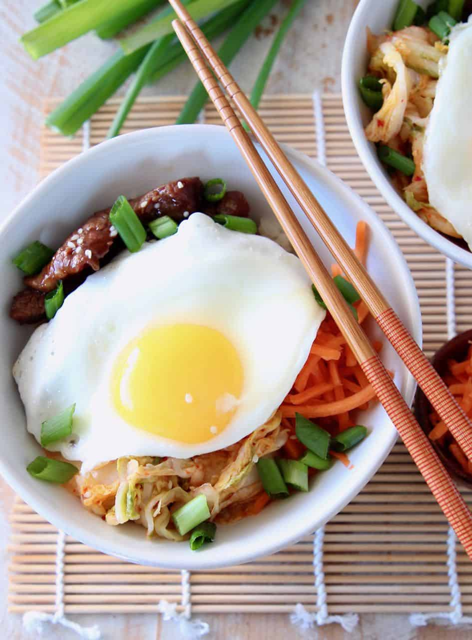 Korean BBQ Cauliflower Rice Bowl topped with a fried egg with chopsticks and green onions