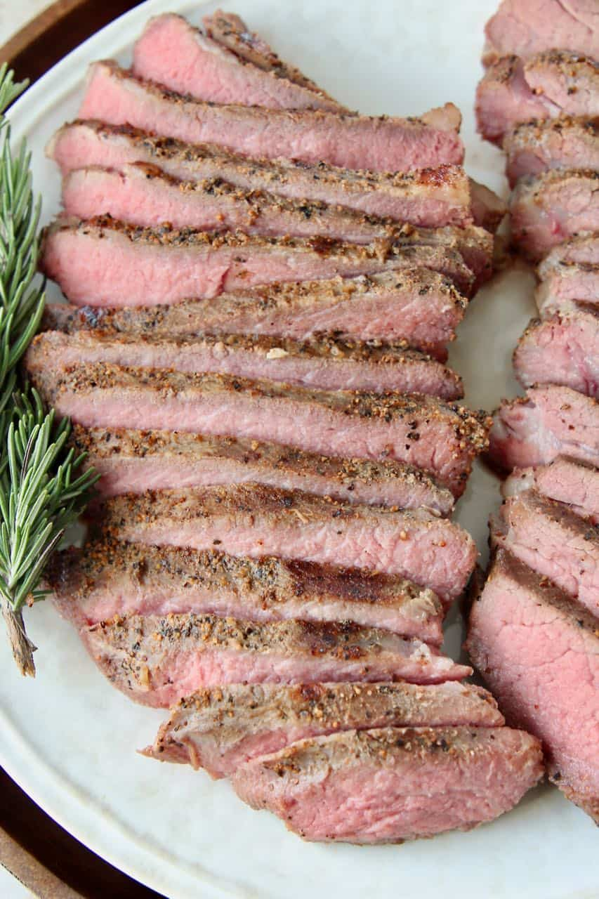 Sliced sous vide tri tip steak on plate with rosemary sprigs