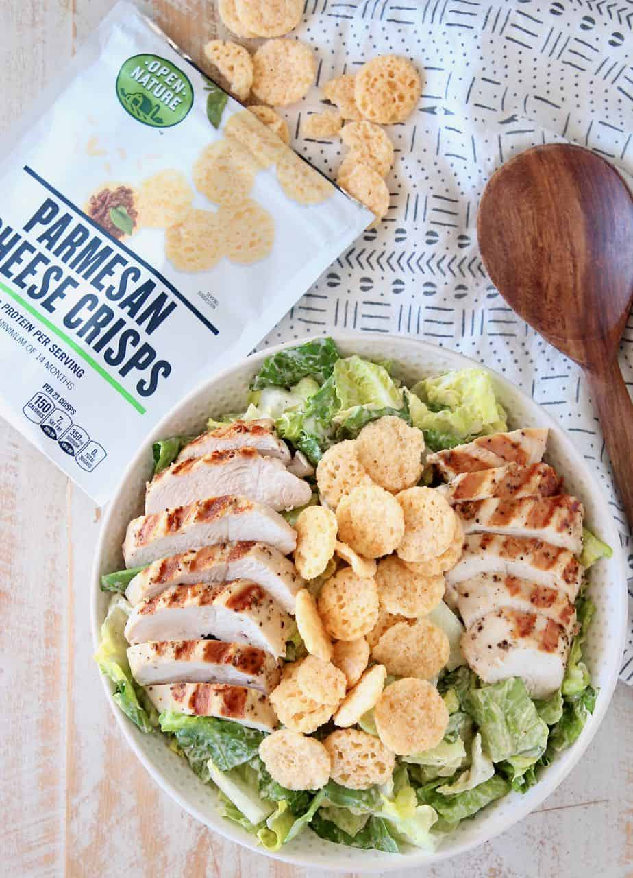Salad in bowl topped with sliced grilled chicken and parmesan crisps
