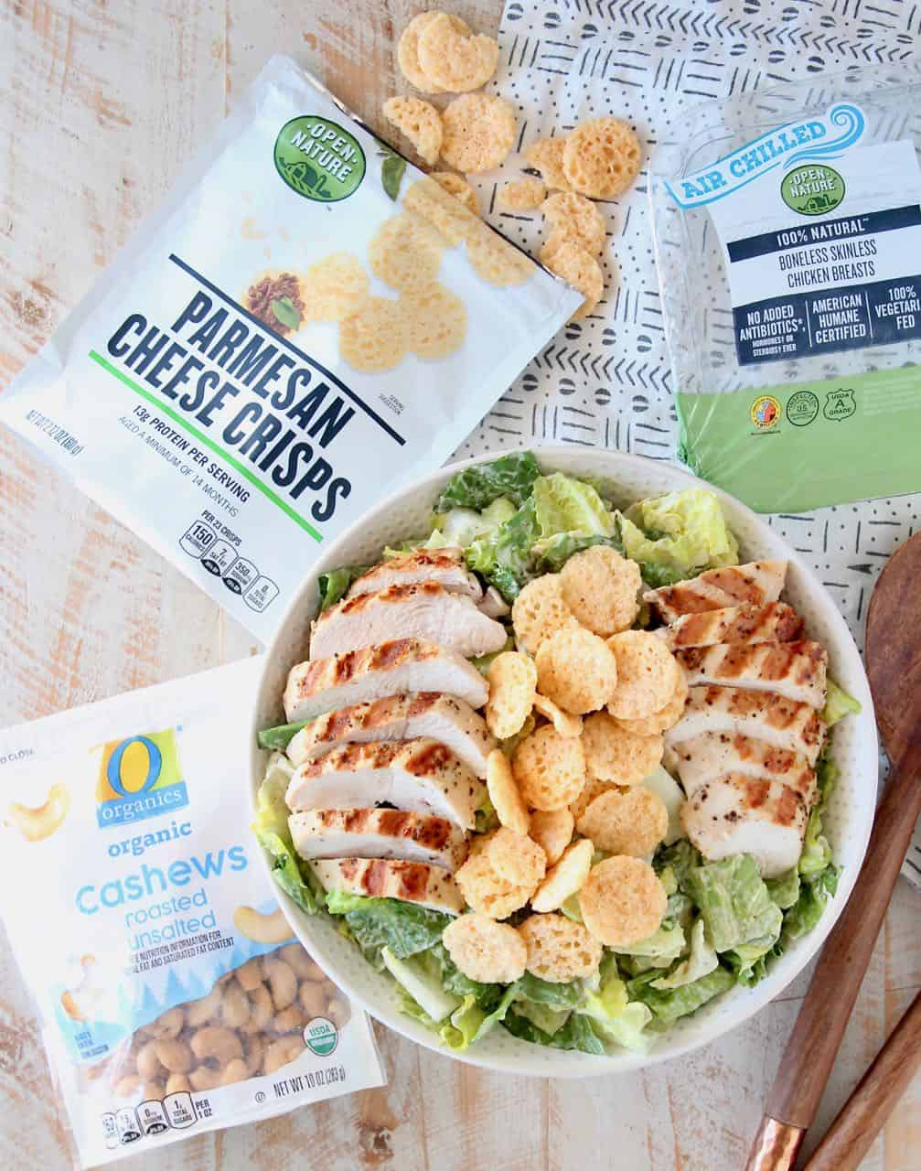 Grilled chicken caesar salad in bowl topped with parmesan cheese crisps