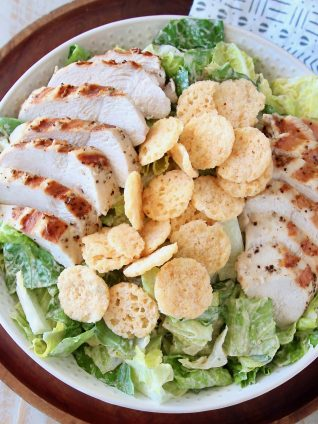 Grilled chicken caesar salad in bowl with parmesan cheese crisps on top