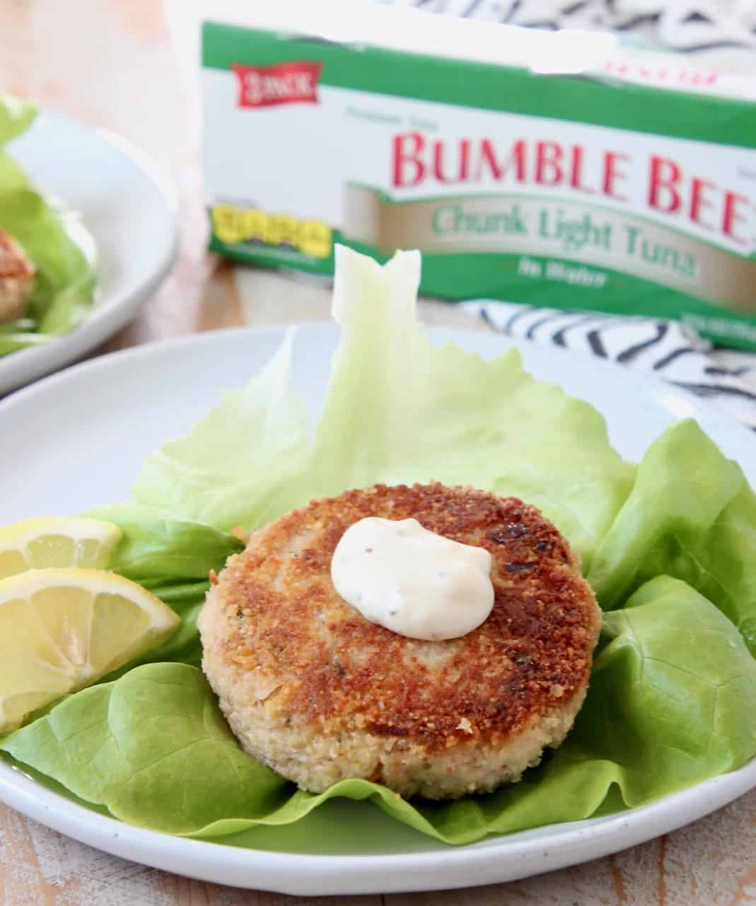 Tuna patty on leaf of lettuce with lemon wedges on plate