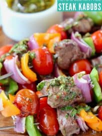 Steak and veggie skewers stacked up on wood serving tray