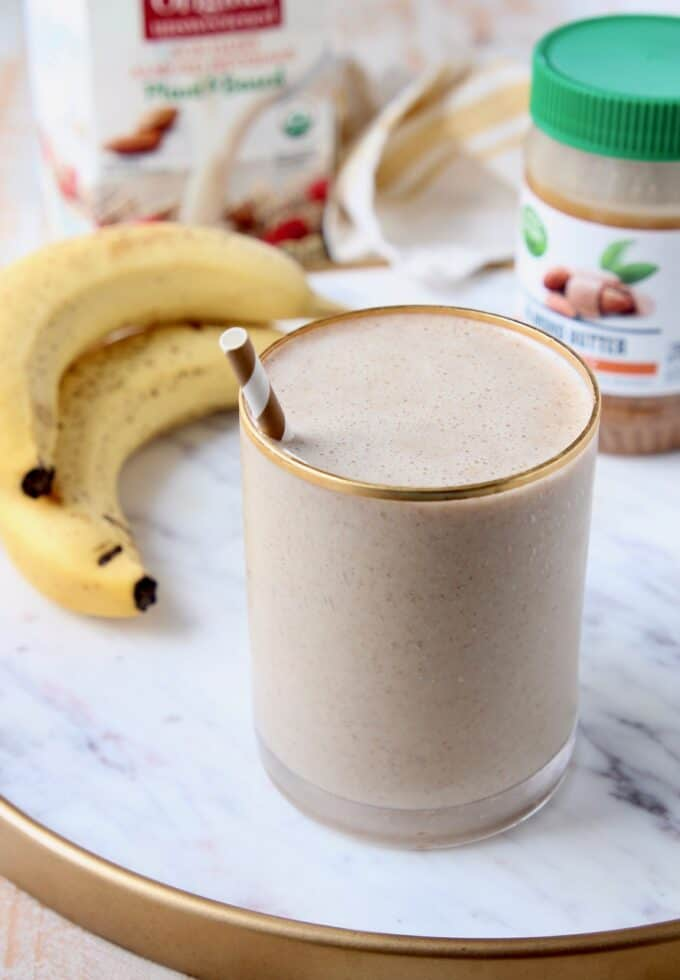 banana almond milk smoothie in glass with straw