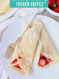 Crepes rolled up on plate filled with nutella and sliced strawberries