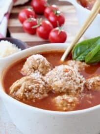 Meatball soup in bowl with gold spoon and fresh basil leaves