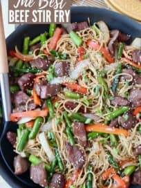 Overhead image of beef stir fry with noodles in skillet with spoon