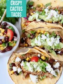 Overhead image of three tacos on plate with a side of salsa