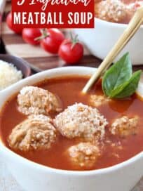 Meatballs in tomato soup in bowl with spoon