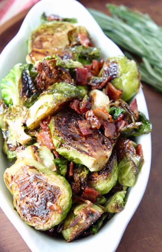 cooked brussels sprouts and bacon in white serving dish