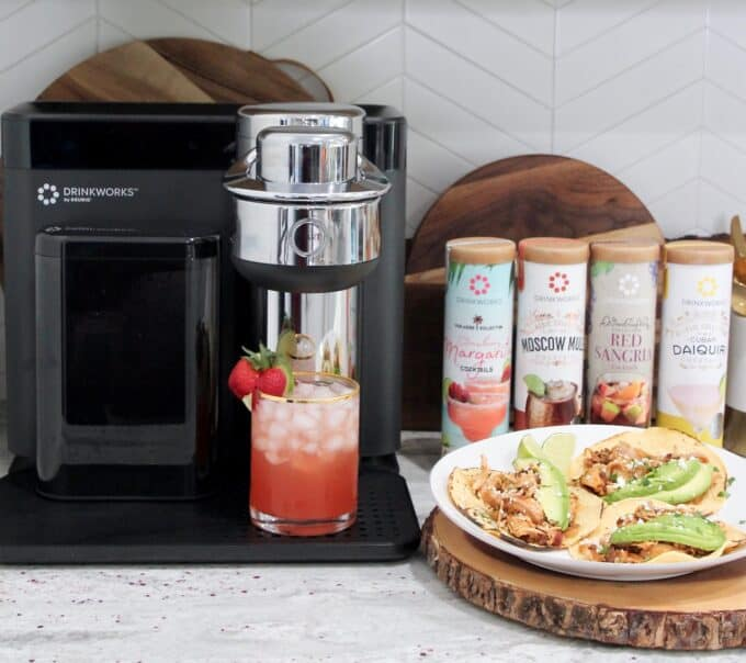 tacos on plate sitting next to drinkworks appliance with a strawberry margarita