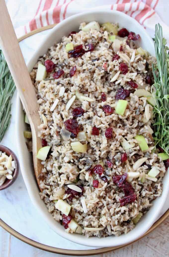 overhead image of wild rice pilaf in serving dish with wooden serving spoon