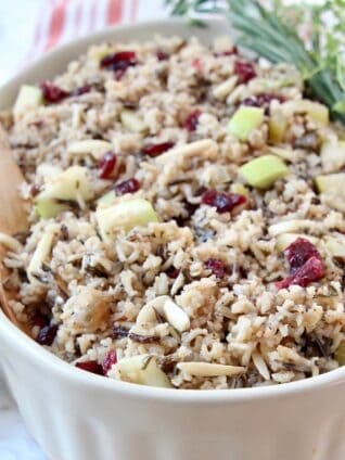 wild rice pilaf in serving dish with wooden serving spoon